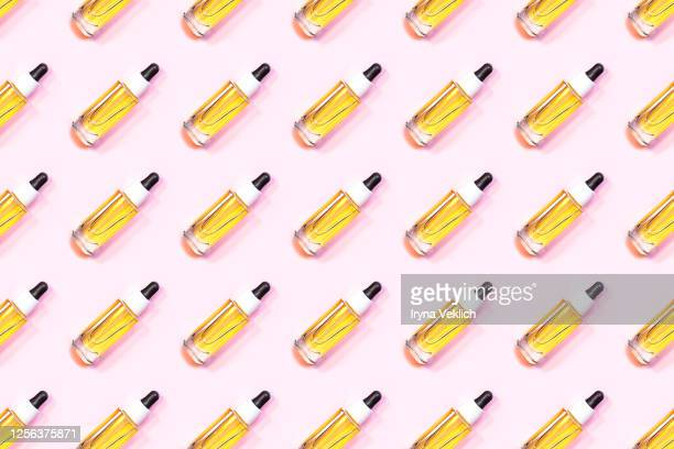 pattern made of glass bottle of oil with a pipette or face serum on a pastel pink background. - cbd oil stock pictures, royalty-free photos & images
