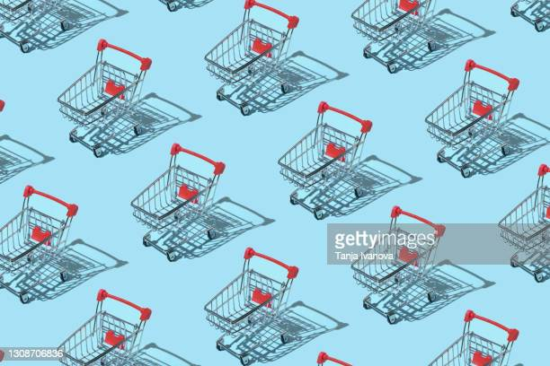 pattern made of shopping trolley on blue background. shopping and sale concept. flat lay, top view - supermarket stock pictures, royalty-free photos & images