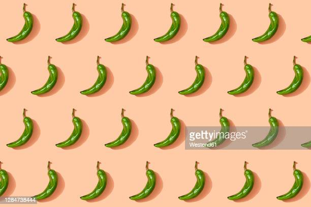 pattern of green chili peppers - green chili pepper stock pictures, royalty-free photos & images