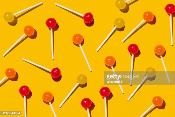 pattern of lollipops against yellow background - lollipop stock pictures, royalty-free photos & images