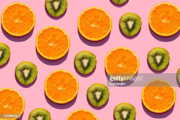 pattern of orange and kiwi fruit slices against pink background - kiwi fruit stock pictures, royalty-free photos & images