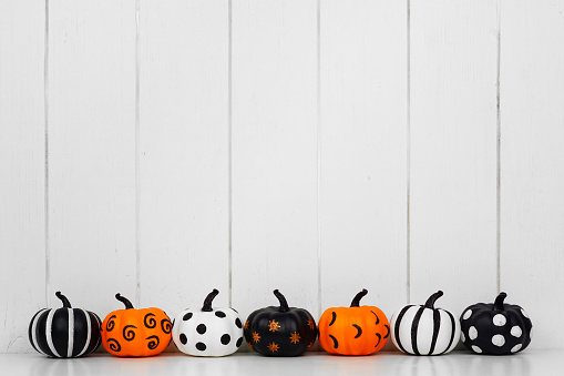 Patterned Halloween pumpkins in a row against a white wood background 1174282750