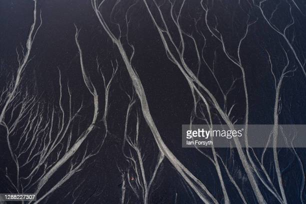 Patterns are left as sea water drains through sea coal deposited on Saltburn beach on November 28, 2020 in Saltburn By The Sea, England. Sea coal...