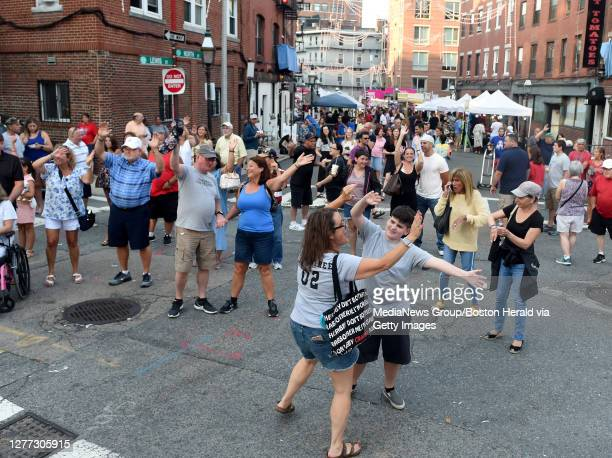 Patti Crabtree of Lowell, with her son John behind them Peter and Janet MacFarland of the England, dance in the street to an oldies group, during the...