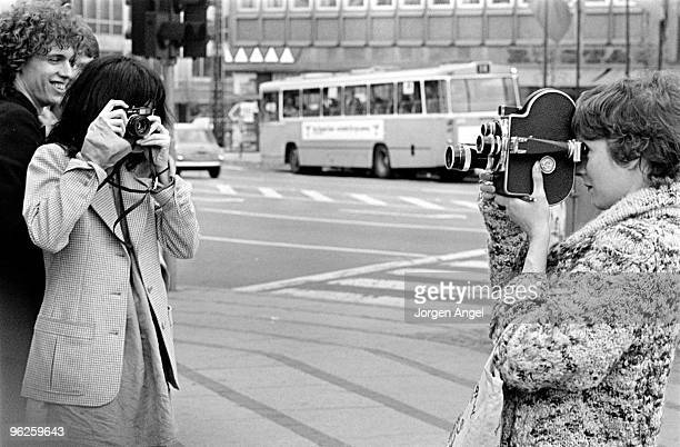 Patti Smith poses for a portrait with Richard Sohl taking pictures of a tourist with her Leica camera in May 1976 in Copenhagen Denmark