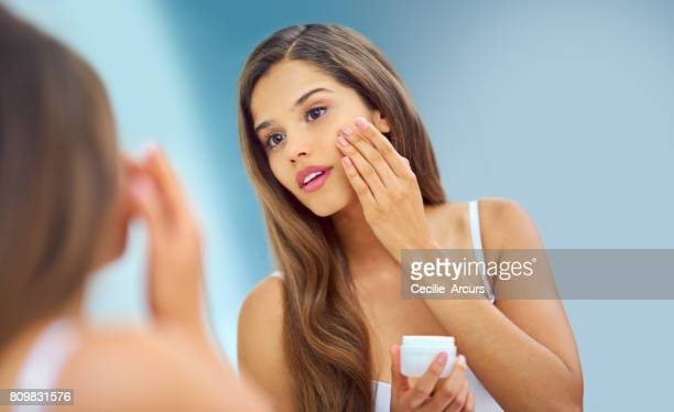 patting on some obligatory moisturizer - human skin stock pictures, royalty-free photos & images
