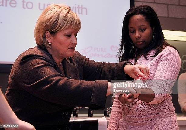 Patty Brisben left founder and chief executive officer of Pure Romance Inc demonstrates a flavored waterbased personal lubricant on Nicole Maynard a...