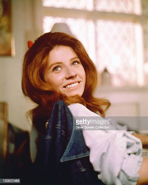 Patty Duke US actress smiling as she turns her head toward the camera for a portrait while sitting in a chair with a denim jacket on the backrest...