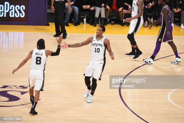 Patty Mills of the San Antonio Spurs highfives DeMar DeRozan of the San Antonio Spurs against the Los Angeles Lakers on December 5 2018 at STAPLES...