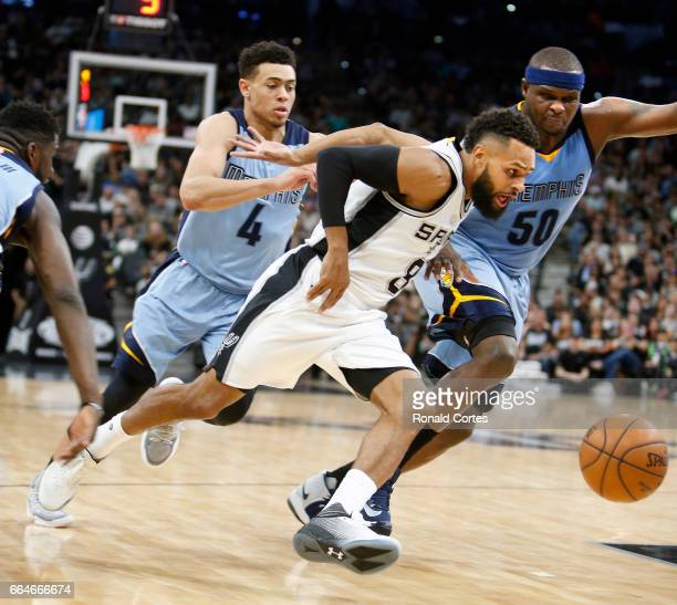 Patty Mills of the San Antonio Spurs pushes the ball against Wade Baldwin IV of the Memphis Grizzlies and Zach Randolph of the Memphis Grizzlies at...