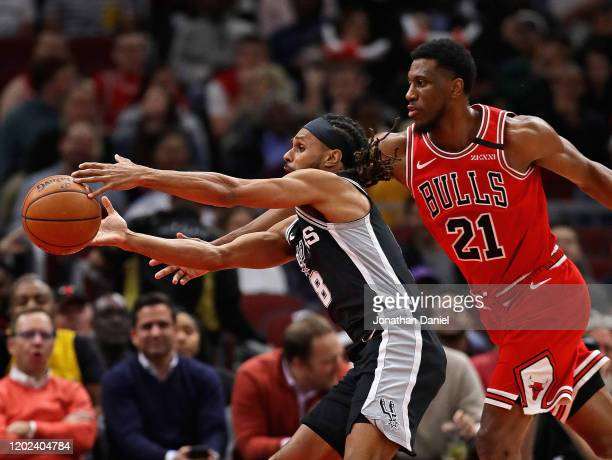 Patty Mills of the San Antonio Spurs reaches for a pass under pressure from Thaddeus Young of the Chicago Bulls at the United Center on January 27...