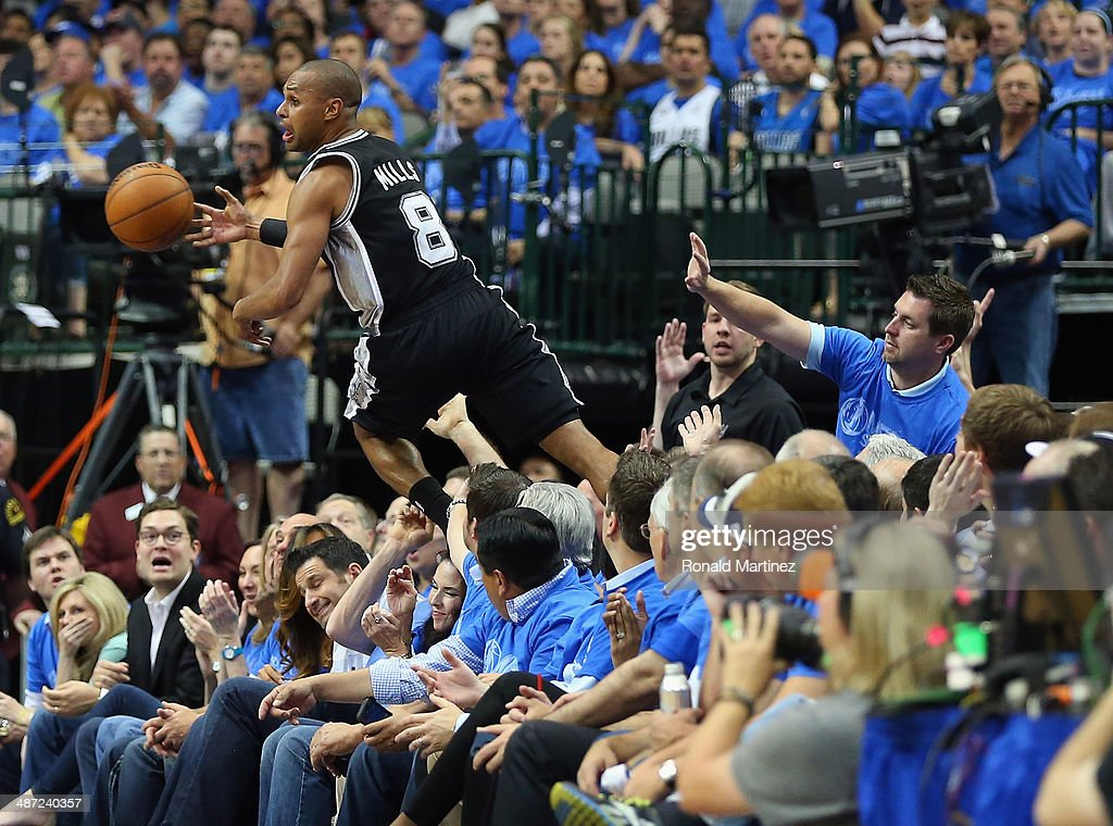 Patty Mills #8 of the San Antonio Spurs saves the ball from falling out of bounds as he jumps over fans against the Dallas Mavericks in Game Four of the Western Conference Quarterfinals during the 2014 NBA Playoffs at American Airlines Center on April 28, 2014 in Dallas, Texas.