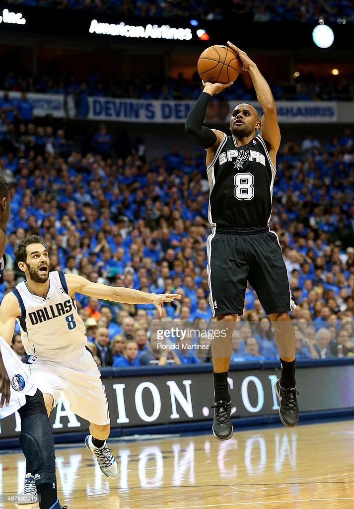Patty Mills #8 of the San Antonio Spurs takes a shot against Jose Calderon #8 of the Dallas Mavericks in Game Four of the Western Conference Quarterfinals during the 2014 NBA Playoffs at American Airlines Center on April 28, 2014 in Dallas, Texas.