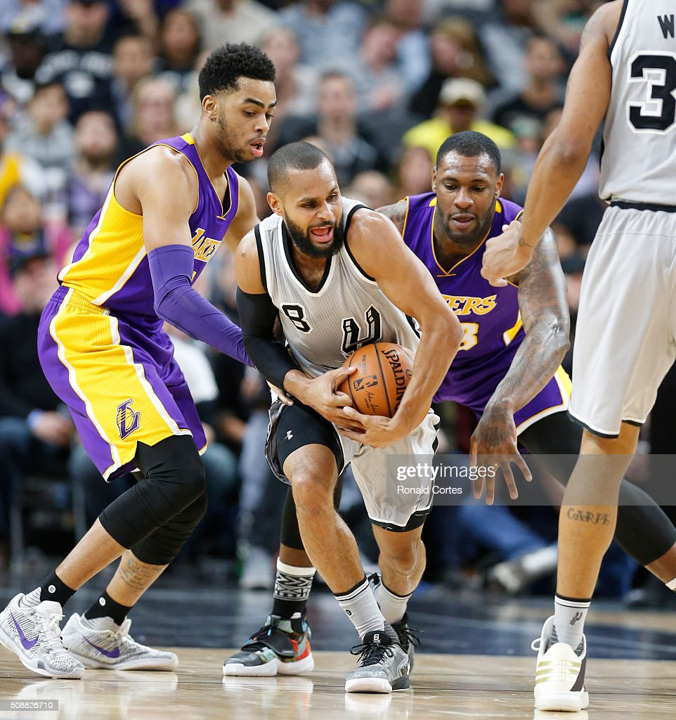 Patty Mills #8 of the San Antonio Spurs tries to keep the ball away from D'Angelo Russell #1 of the Los Angeles Lakers at AT&T Center on February 6, 2016 in San Antonio, Texas.