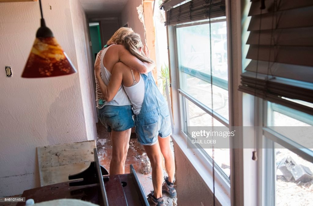 TOPSHOT - Patty Purdo (L) hugs a friend as she surveys the damage caused to her trailer home from Hurricane Irma at the Seabreeze Trailer Park in Islamorada, in the Florida Keys, September 12, 2017. /