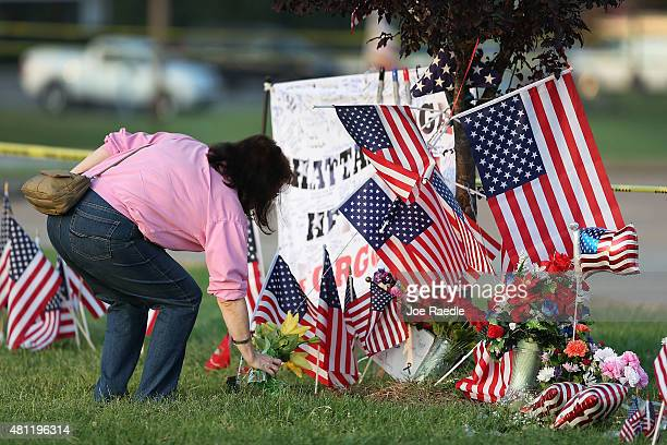 Patty Storm places flowers in a memorial setup in front of the Armed Forces Career Center/National Guard Recruitment Office on July 18 2015 in...