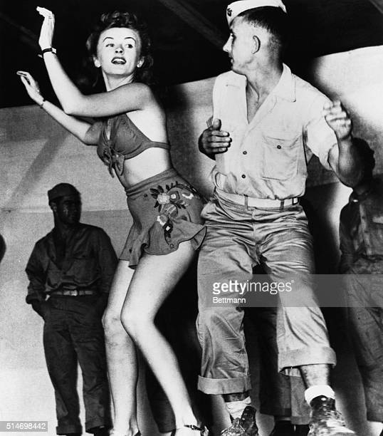 Patty Thomas, a dancer with Bob Hope's USO tour in the South Pacific, dances with a US Marine during World War II. | Location: southern Pacific Ocean.