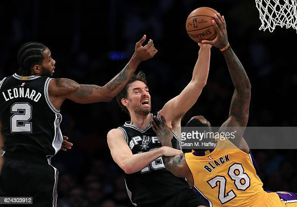 Pau Gasol and Kawhi Leonard of the San Antonio Spurs defend against a shot by Tarik Black of the Los Angeles Lakers during the second half of a game...