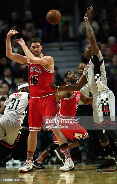 Pau Gasol of the Chicago Bulls passes the ball over his head to teammate E'Twaun Moore under pressure from Dwight Howard of the Houston Rockets at...