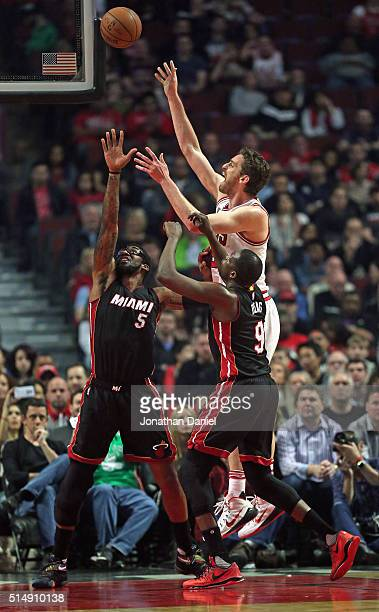 Pau Gasol of the Chicago Bulls shoots over Amar'e Stoudemire and Luol Deng of the Miami Heat at the United Center on March 11 2016 in Chicago...