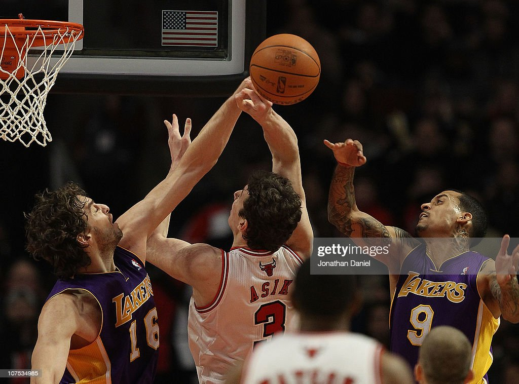 Pau Gasol #16 of the Los Angeles Lakers knocks the ball away from Omer Asik #3 of the Chicago Bulls as Matt Barnes #9 defends at the United Center on December 10, 2010 in Chicago, Illinois. The Bulls defeated the Lakers 88-84.