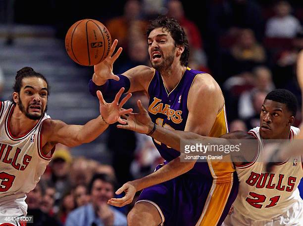 Pau Gasol of the Los Angeles Lakers passes the ball under pressure from Joakim Noah and Jimmy Butler of the Chicago Bulls at the United Center on...