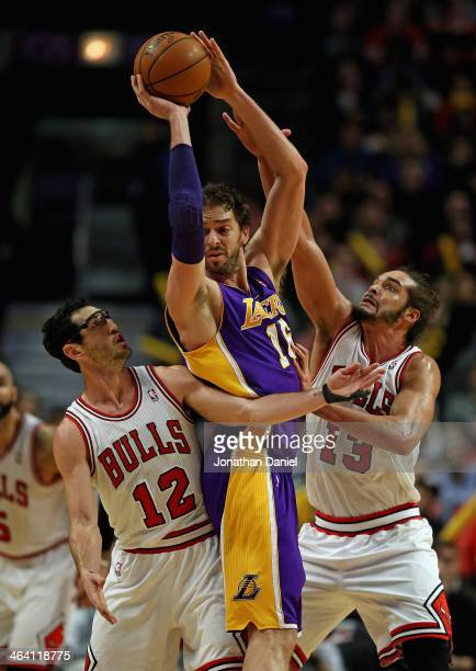 Pau Gasol of the Los Angeles Lakers tries to pass under pressure from Kirk Hinrich and Joakim Noah of the Chicago Bulls at the United Center on...