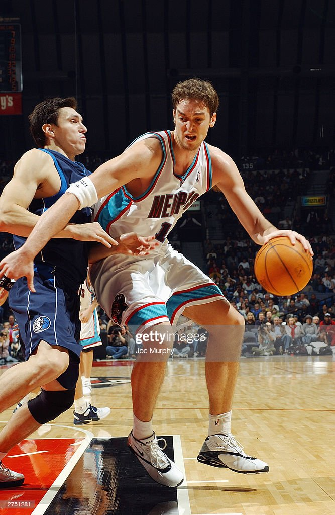 Pau Gasol #12 of the Memphis Grizzlies has the ball in the post against Eduardo Najera #14 of the Dallas Mavericks at The Pyramid on November 15, 2003 in Memphis, Tennessee. The Grizzlies won in overtime 108-101.