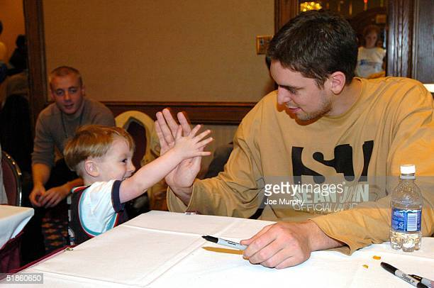 Pau Gasol of the Memphis Grizzlies high fives a young fan during the Holiday Toy Drive at the Hilton Hotel on December 14 2004 in Memphis Tennessee...