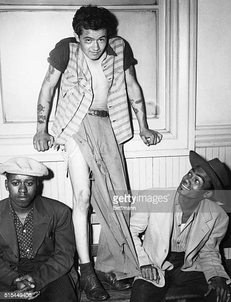 Paul Acevedo stands in his tattered clothing flanked by two men in zoot suits following the 'Battle of Gangland' in Los Angeles California Since May...