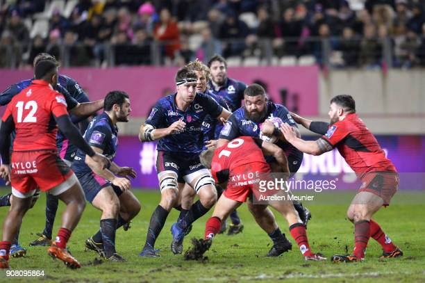 Paul Alo Emile of Stade Francais is tackled by Jaco Van Der Walt of Edinburgh during the European Rugby Challenge Cup match between Stade Francais...