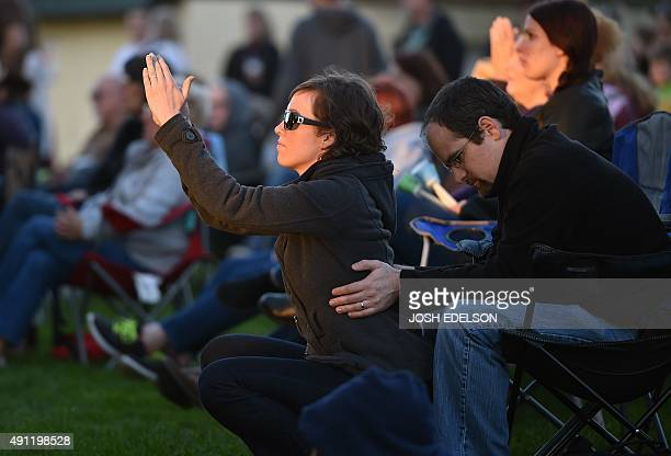 Paul and Hannah Spagnola react to religious music during a vigil for the victims of the Umpqua Community College shooting in Winston Oregon on...