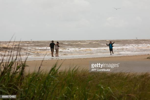 Paul and Roberta Whitehat and their son Dylan of Arizona walk on the beach collecting seashells and enjoying the rough surf in the aftermath of...