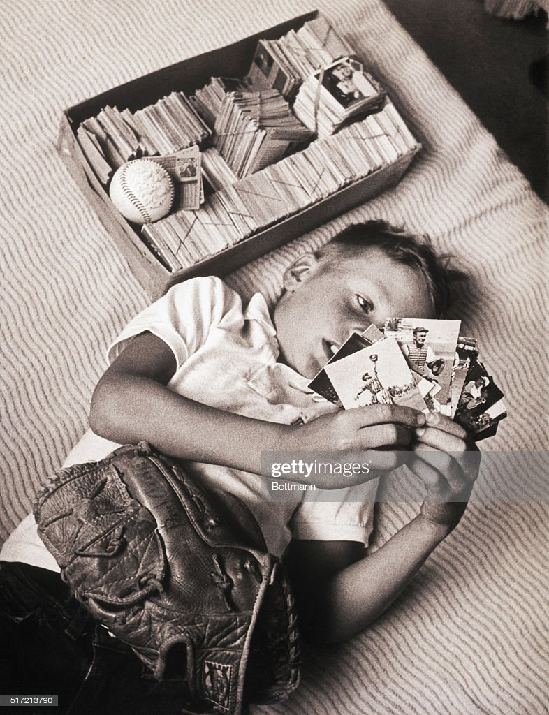 Boy Lying on Bed Studying Baseball Cards : News Photo