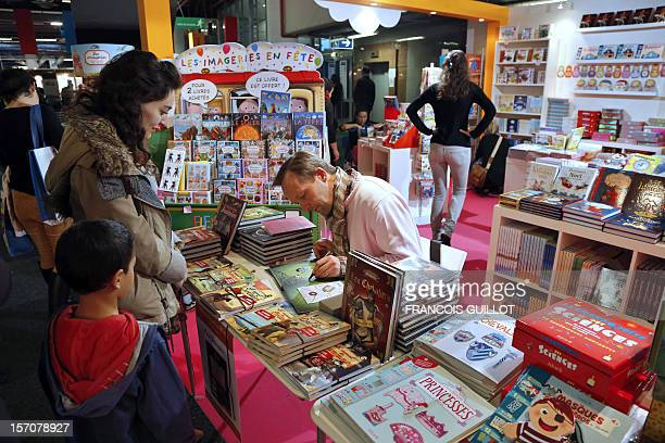 Paul Beaurepere comic book artist signs one of his books at the Books and press for Youth fair on November 28 2012 in Montreuil outside Paris AFP...