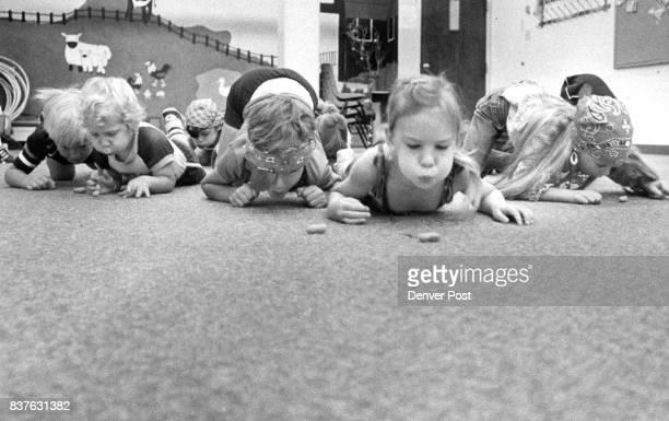 Paul Beck Rec Kids Treasure Hunt kids blowing Panuts accross the room Credit The Denver Post