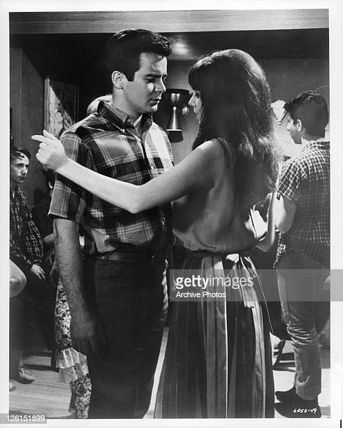 Paul Bertoya and Laurie Mock gazing into one anothers eyes in a scene from the film 'Hot Rods To Hell' 1966