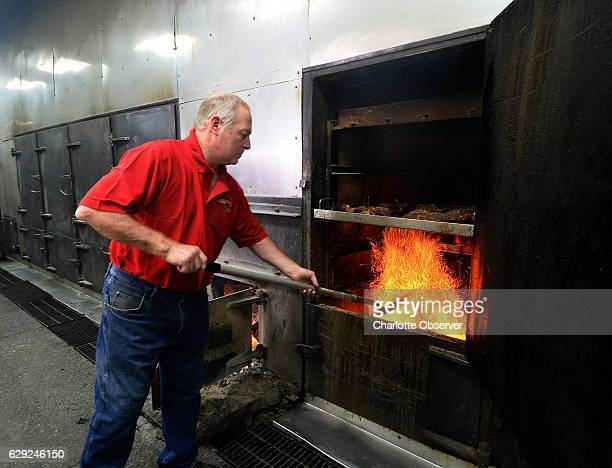 Paul Bessinger Sr adds hot coals from the fire as he cooks brisket in the barbecue pits at the original Piggie Park location on Charleston Highway in...