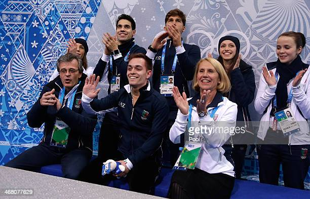Paul Bonifacio Parkinson of Italy waits with teammates and coaches for his score in the Men's Figure Skating Men's Free Skate during day two of the...
