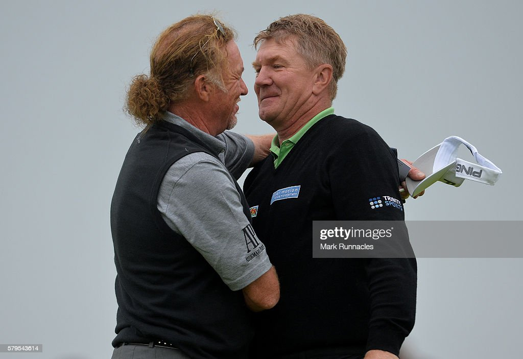 Paul Broadhurst (R), of England is embraced by playing partner Miguel Angel Jimenez of Spain after his final putt on 18 to win The Senior Open Championship at Carnoustie Golf Club on July 24, 2016 in Carnoustie, Scotland.