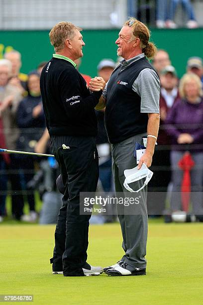 Paul Broadhurst of England shake hands with Miguel Angel Jimenez on the 18th green during the final round of the Senior Open Championship played at...