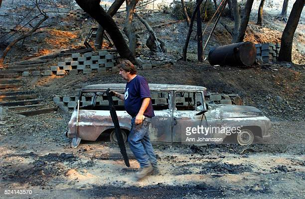 Paul Buchanan walks by a burnt out car in Palmer Canyon north of Claremont NO SALES NEWSPAPERS IN NEW MEXICO | Location Palmer Canyon California...