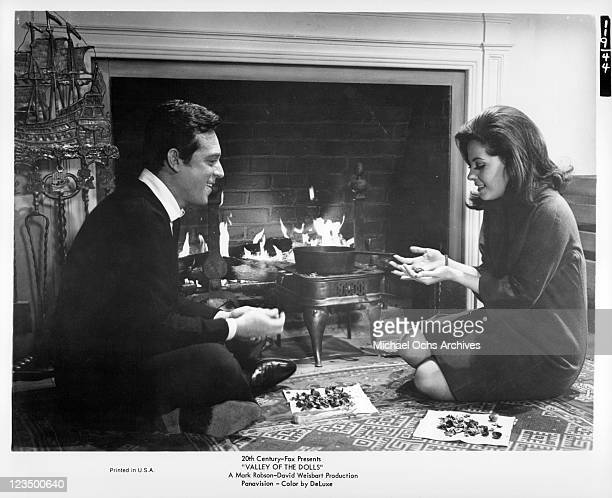 Paul Burke and Barbara Parkins sharing nuts by the fire in a scene from the film 'Valley Of The Dolls', 1967.