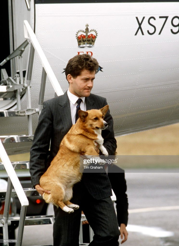 Paul Burrell, A Member Of The Queens Staff, Carrying One Of The Queen's Corgis Off The Royal Flight Aircraft Returning From Balmoral After The Summer Holidays.