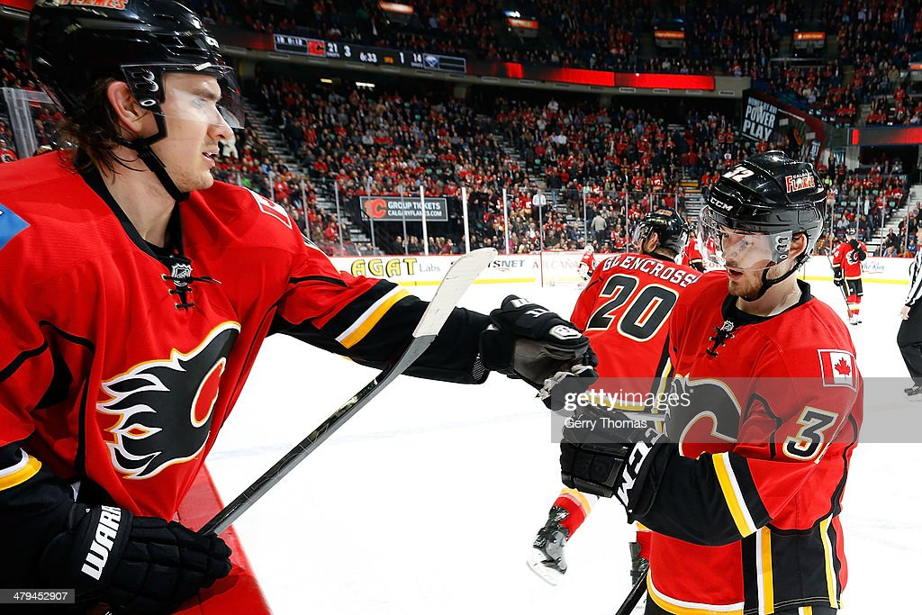 Paul Byron #32 and Mikael Backlund #11 of the Calgary Flames celebrate a goal against the Buffalo Sabres at Scotiabank Saddledome on March 18, 2014 in Calgary, Alberta, Canada.
