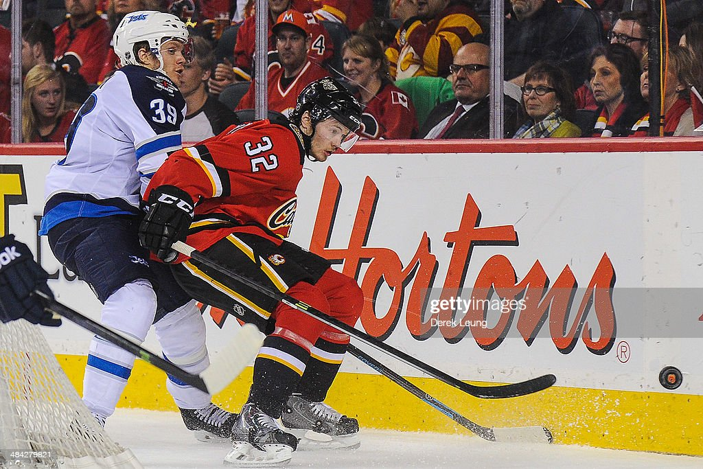 Paul Byron #32 of the Calgary Flames battles for the puck against Tobias Enstrom #39 of the Winnipeg Jets during an NHL game at Scotiabank Saddledome on April 11, 2014 in Calgary, Alberta, Canada. The Jets defeated the Flames 5-3.