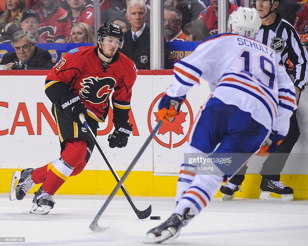 Paul Byron #32 of the Calgary Flames carries the puck against Justin Schultz #19 of the Edmonton Oilers during an NHL game at Scotiabank Saddledome on January 31, 2015 in Calgary, Alberta, Canada. The Flames defeated the Oilers 4-2.
