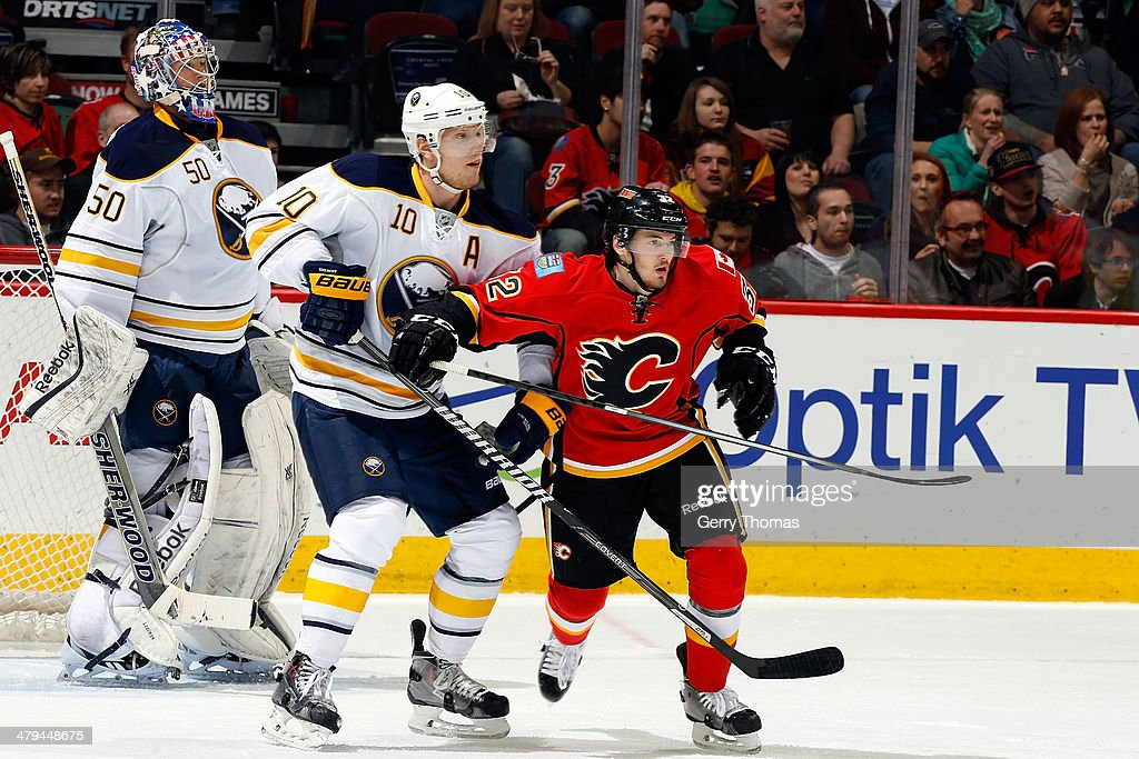 Paul Byron #32 of the Calgary Flames skates against Christian Ehrhoff #10 of the Buffalo Sabres at Scotiabank Saddledome on March 18, 2014 in Calgary, Alberta, Canada.
