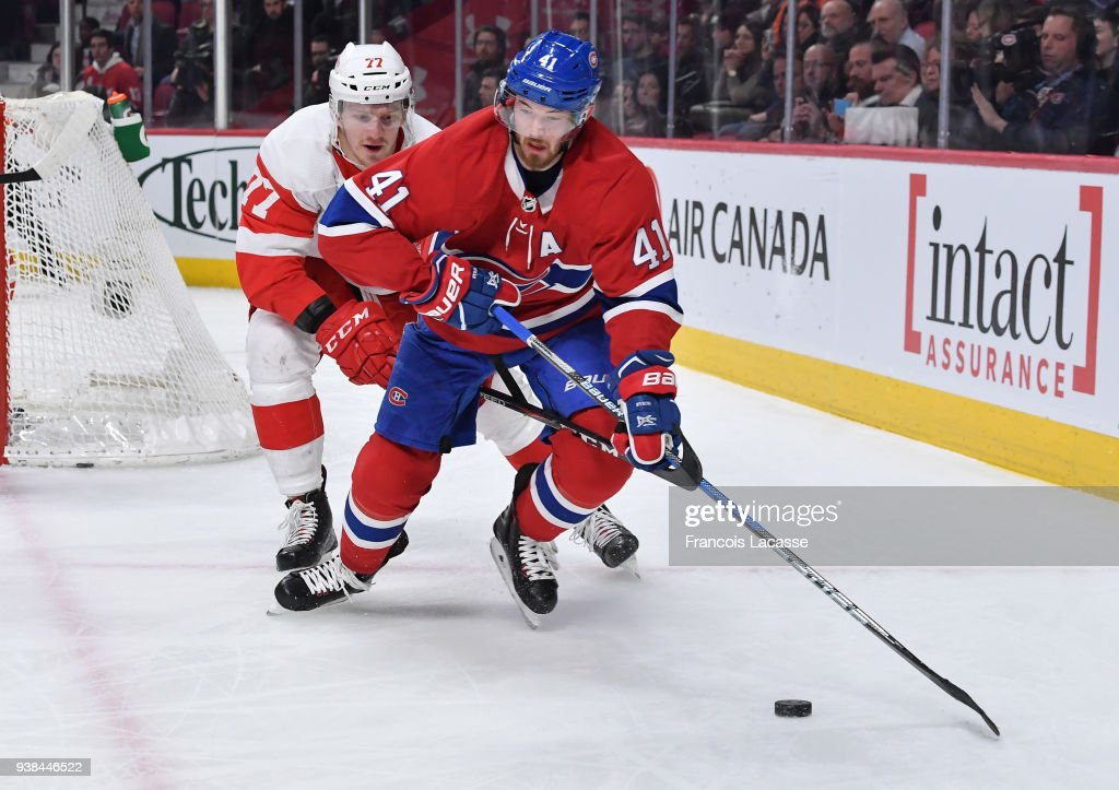 Paul Byron #41 of the Montreal Canadiens controls the puck while being challenged by Evgeny Svechnikov #77 of the Detroit Red Wings in the NHL game at the Bell Centre on March 26, 2018 in Montreal, Quebec, Canada.