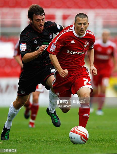 Paul Caddis of Swindon Town battles for the ball with Joe Heath of Hereford United during the npower League Two match between Swindon Town and...